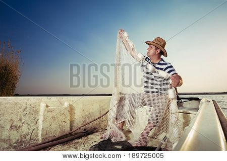 The old fisherman checks fishing net on the boat