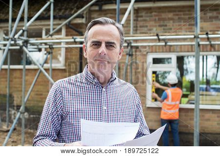 Satisfied Client Looking At Bills For House Building Work