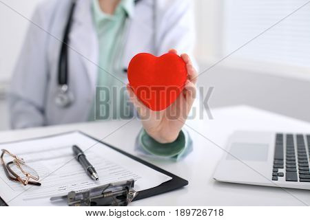 Female doctor with stethoscope holding heart. Cardio therapeutist, physician make cardiac physical, heart rate measure, arrhythmia, old age life concept.