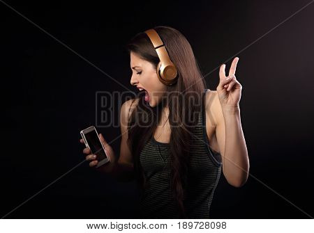 Beautiful Dancing Young Woman Listening The Music, Showing V Sign By Hand In Wireless Headphone And