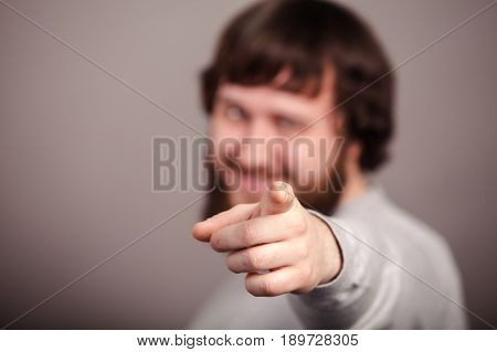 Happy businessman pointing his finger on you, close-up.