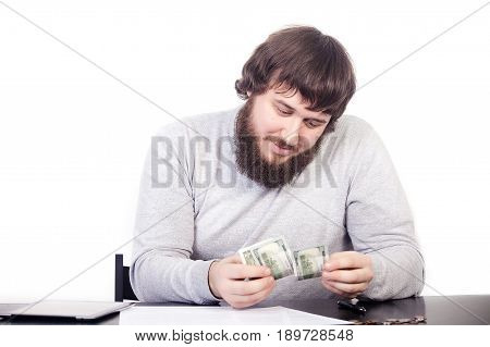 Money doesn't bring buy happiness. Close Up portrait young man holding money cash, human looks at cash, sitting at the table, isolate white background.