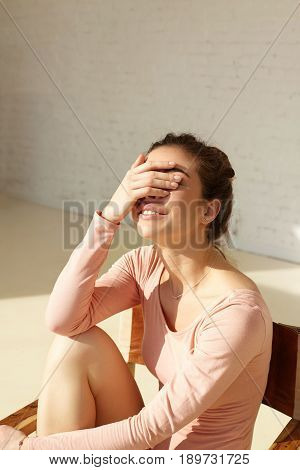 Attractive girl with cute smile covers face by hand squinting eyes in bright sun having fun posing in modern interior at home. Smiling young fashion model enjoying the rest at home copy space wall