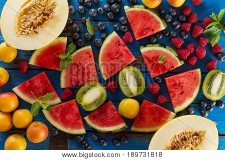 Tasty fresh appetizing assorted fruits on blue rustic old wooden table. Top View. Food Summer Concept. Horizontal.