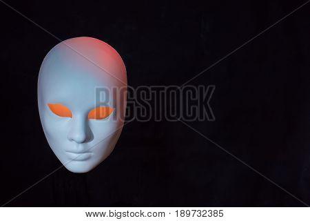 Concept of terrorism.White mask on dark background