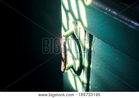 The old door handle in the dark room is lit by the rays of sunlight. Forward to light concept