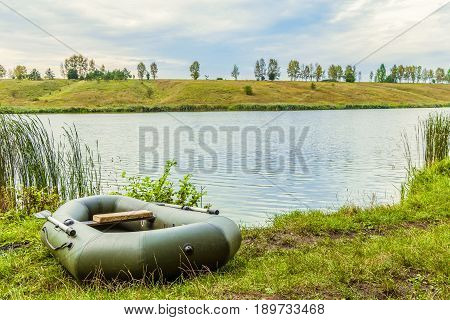 Fishing inflatable rubber boat standing on the shore of lake. Dinghy with oars.