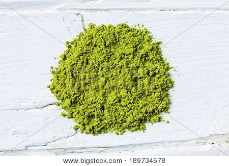 Green matcha tea powder on white wooden background view from above