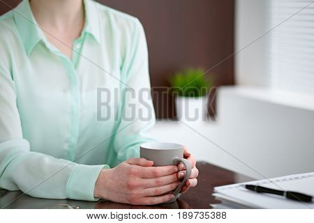 Business woman hands  in a green blouse sitting at the desk in the office and is holding a gray cup, right window. She is  thinking about  business problems , success, concept.