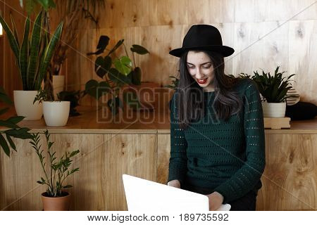 Young freelancer female in trendy hat writing new post in social networks while waiting her breakfast in comfy cafe. Young woman copywriter smiling working on laptop sitting in cafe enjoys her work.