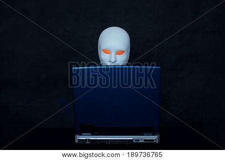 Concept of terrorism.Mask and laptop on dark background