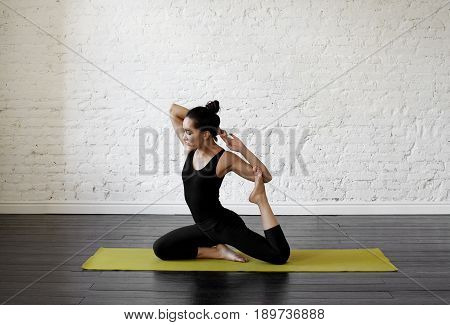 Yoga and health concept. Pretty asian female student doing Eka Pada Rajakapotasana on white wall background in the yoga hall. Calmness and relax woman happiness. Copy space for text