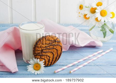 Glass of milk oat cookies with chocolate and bouquet of chamomiles pink napkin and striped straws on wooden background. Summer breakfast background.