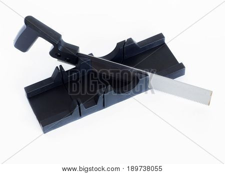 An iron saw and a miter box. A saw from metal with a plastic handle is standing in a miter box.