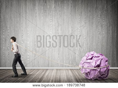 Young man in room making huge paper ball move