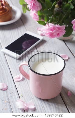 A cup of milk, phone and dogrose on the white wooden table