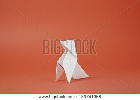 Origami Paper Bird On A Red Background