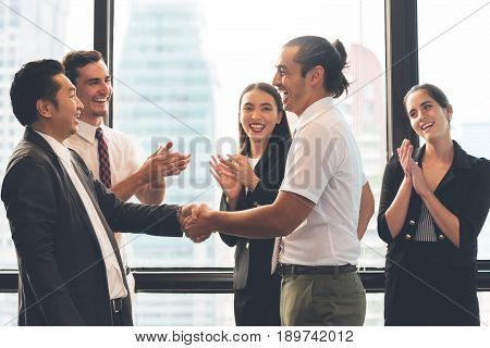 Business People Handshaking after greeting deal with man and women clapping hands background.