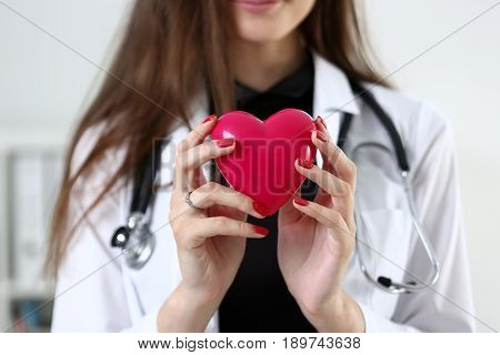 Female Medicine Doctor Hands Holding And Covering Red Toy Heart