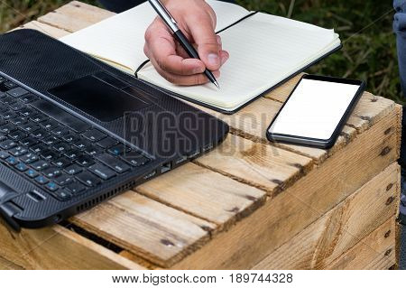 Hand writing in a notepad with laptop and bezel less smartphone with blank screen. Freelance work outside of the office.