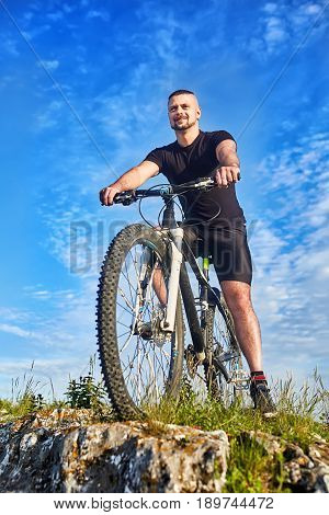 Bottom view of the smiling cyclist with bike against blue sky with clouds. Happy sportsman in the black sportwear and with sportive shoes. Cyclist standing on the rocks. Vertical photo. Concept of the healthy lifestyle.