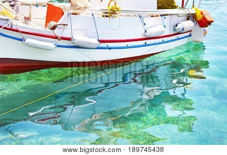 fishing boat reflected on sea Aegina island Greece