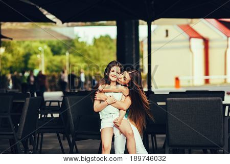 Fashionable mother kissing her daughter sitting in the summer terrace