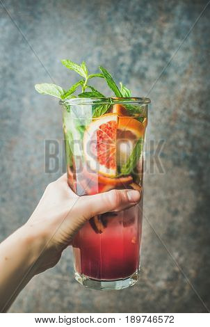 Woman's hand holding glass of blood orange citrus lemonade with mint and ice, dark brown stone background. Refreshing summer drink concept