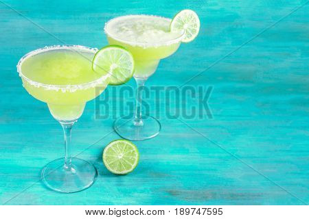 Lemon Margarita cocktails with wedges of lime on a teal background with copy space, toned image
