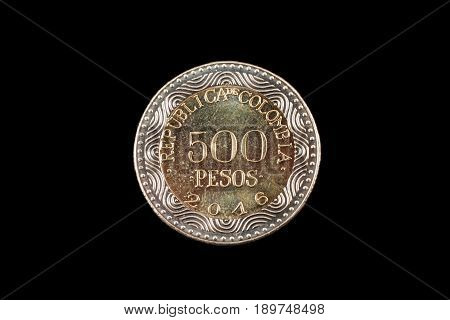 A close up image of a 500 colombian peso coin on a black background
