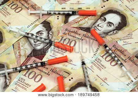 Venezuelan currency close up with hypodermic needles