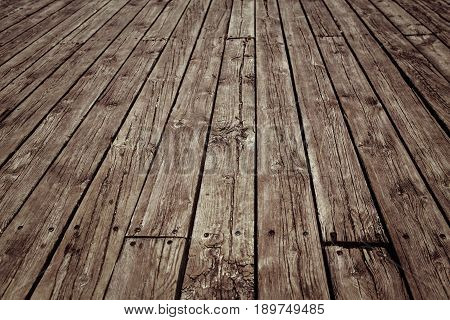 Closeup of brown grunge wooden planks of fence boardwalk diagonal lines. Moody grungy textured background