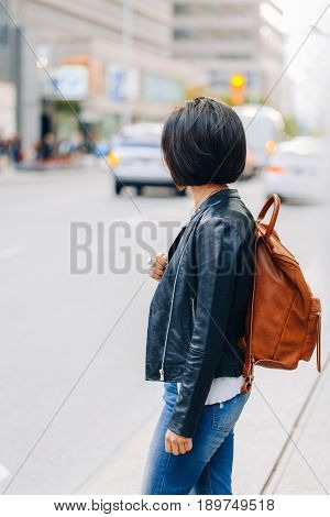 Portrait of young girl woman with short dark hair bob style in blue jeans and leather biker jacket with yellow brown backpack on shoulder standing in city street view from back behind