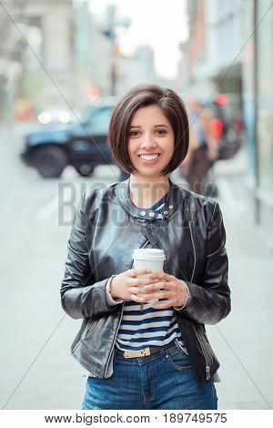 Portrait of beautiful smiling young latin hispanic girl woman with short dark black hair bob holding cup of coffe tea outside looking in camera natural smile emotion ethnic diversity
