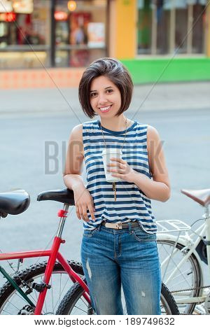 Portrait of beautiful smiling young latin colombian girl woman with short hair bob in blue ripped jeans striped tshirt holding cup of coffee leaning on bike in city ethnic diversity