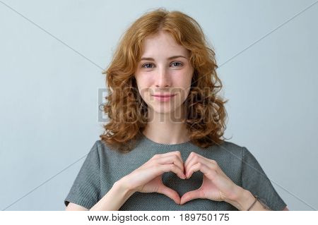 Red-haired Girl With Freckles Shows The Silhouette Of The Heart With The Help Of Hands. Care For Hea