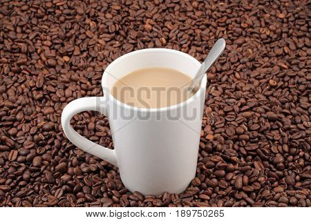 A white coffee cup on a background of whole coffee beans