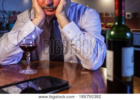 Male businessman drinking after wine working day trying to forget about problems