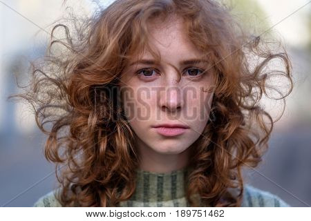 Beautiful Red-haired Girl With Long Curly Hair Gently Looking At The Camera. People And Lifestyle Co