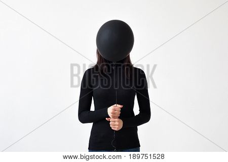 A sad girl holds a black balloon in her hands. She is closing her face because of the loneliness and devastation of the soul