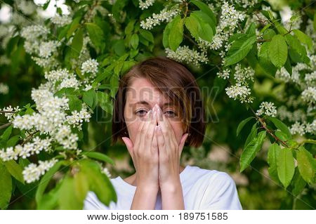 A Beautiful Girl Stands By The Blossoming Bird Cherry And Sneezes. She Suffers From An Allergy To Fl