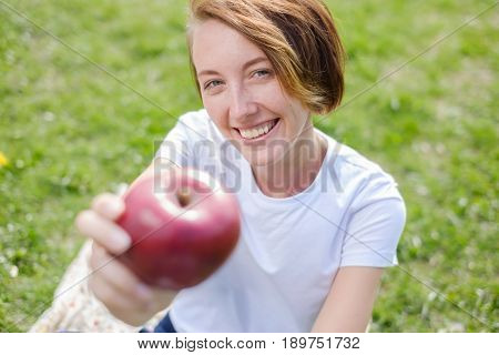 Very beautiful caucasian model eating red apple in the Park. Outdoors portrait of pretty young girl sitting on green grass