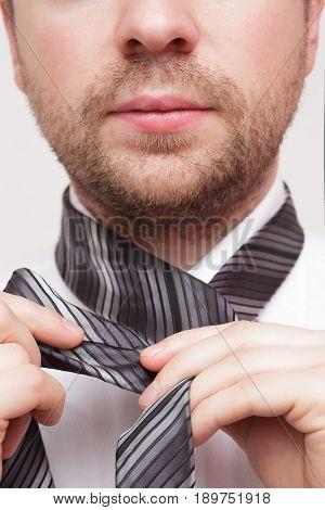 Young businessman adjust necktie to his suit