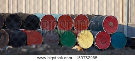 Colorful fifty gallon metal drums seen on end with one row stacked on the other against a metal building. Shallow depth of field.