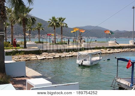 31st MAY 2017, CALIS, TURKEY:English tourists looking at large ornamental flowers along the promenade between calis and fethiye in turkey, 31st may 2017