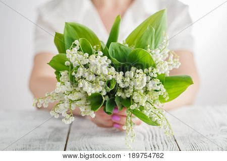Woman Holding Bouquet Of Lily Of The Valley Flowers
