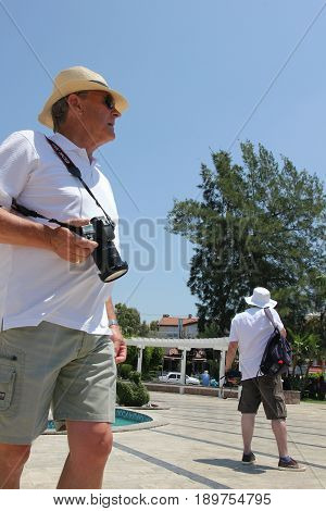 31ST MAY 2017,FETHIYE, TURKEY: Unknown english tourists with cameras along the promenade in fethiye, turkey, 31st may 2017