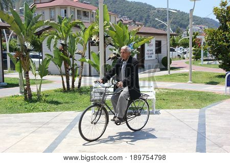 31ST MAY 2017,FETHIYE, TURKEY: An unknown elderly man riding his cycle along the promenade in fethiye in turkey,31st may 2017