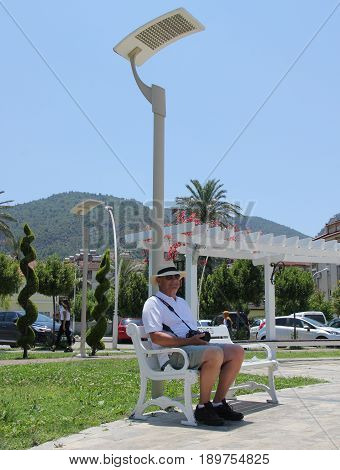 31ST MAY 2017,FETHIYE,TURKEY: An unknown englishman sitting in the shade along the promenade in fethiye , in turkey,31st may 2017