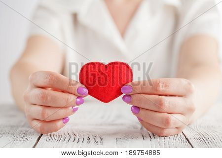 Woman hands holding a soft heart shape